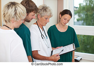 Doctor Explaining Patient Record - Senior female doctor...