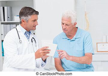 Doctor explaining prescription - Male doctor explaining ...