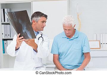 Doctor explaining x-ray - Male doctor explaining x-ray while...