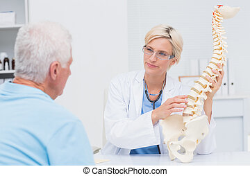 Doctor explaning anatomical spine to male patient - Female...