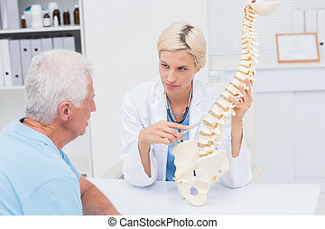 Doctor explaning spine model to senior patient