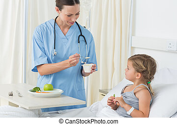 Doctor feeding meal to sick girl