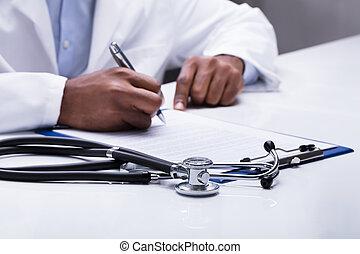 Doctor Filling Form Over The Desk
