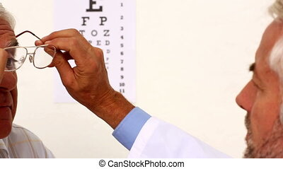 Doctor fitting glasses onto an elde