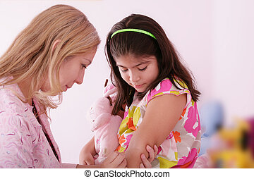 Doctor give injection to girl's arm, focus on the little girl.