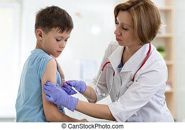 Doctor gives injection to boy's arm