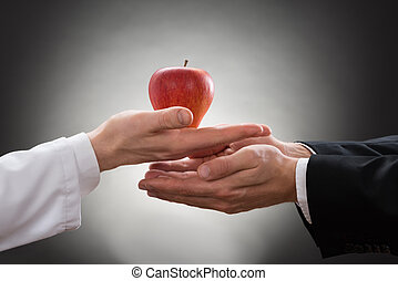 Doctor Giving Apple To A Person