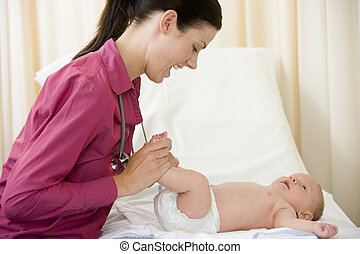 Doctor giving checkup to baby in exam room smiling