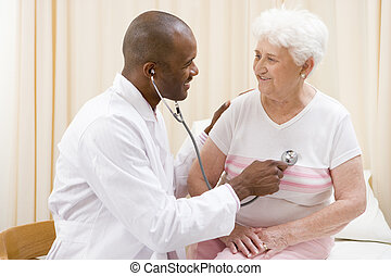 Doctor giving checkup with stethoscope to woman in exam room...