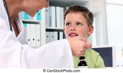 Doctor giving little boy a spoon of medicine