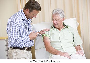 Doctor giving man needle in exam room