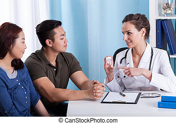 Doctor giving medicines to diverse couple