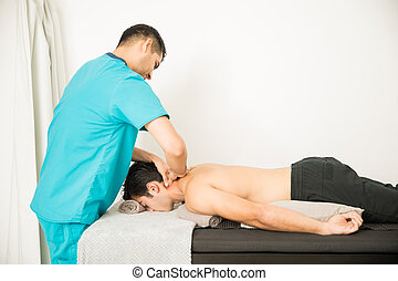 Doctor Giving Physical Therapy To Shirtless Athlete Lying In Bed