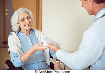 Doctor giving pills his patient
