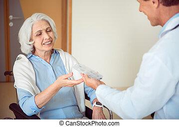 Doctor giving pills his patient