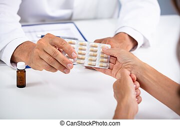 Doctor Giving Pills In Blister To Patient