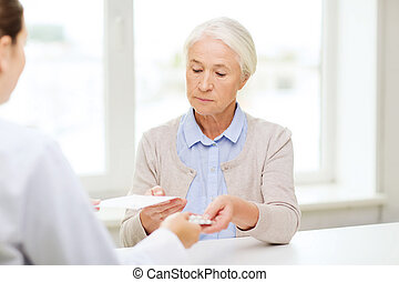 doctor giving prescription and drug to woman