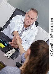 doctor greeting a patient with a handshake in his office