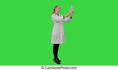 Doctor greeting medical partenrs and have a conversation online via tablet on a Green Screen, Chroma Key.