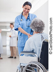 Doctor greeting recovering senior patient in wheelchair in a...