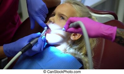 Doctor hands working with drill. Girl child open mouth during drilling caries in teeth. Camera motion shot with gimbal.