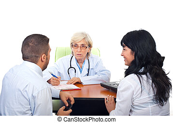 Doctor having conversation with young couple - Senior doctor...