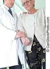 Doctor helping an elderly woman use a crutch