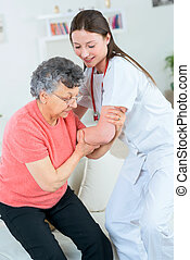 Doctor helping an old lady to stand