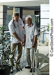 Doctor helping elderly man to walk on crutches.