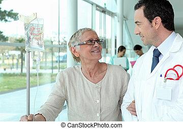 Doctor helping elderly patient in hall