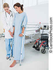 Doctor helping patient in crutches at hospital