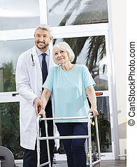 Doctor Helping Senior Female Patient With Walker In Fitness Stud