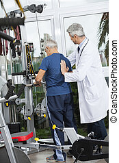 Doctor Helping Senior Man To Use Exercise Machine