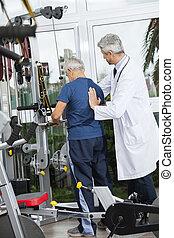 Doctor Helping Senior Man To Use Exercise Machine