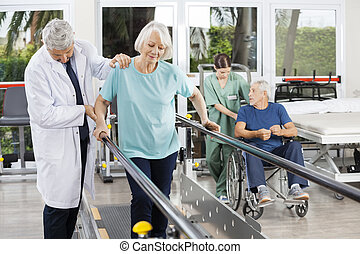 Doctor Helping Woman To Walk Between Bars In Fitness Center...