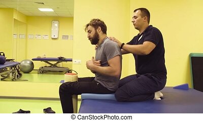 Doctor helping young man at the rehabilitation center -...
