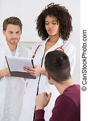doctor holding a clipboard with a patient medical record chart