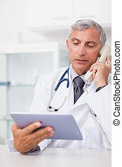 Doctor holding a tablet computer while calling in hospital...