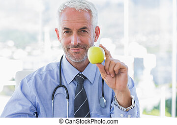 Doctor holding an apple in his hand