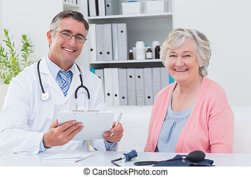 Doctor holding clipboard while sitting with senior patient