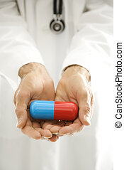 Doctor holding giant pill. - Mid-adult Caucasian male doctor...