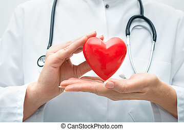 Doctor holding heart - Female doctor with the stethoscope...