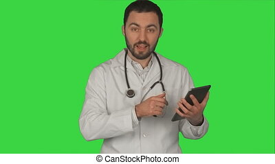 Doctor holding his tablet pc and looking at camera in medical office on a Green Screen, Chroma Key