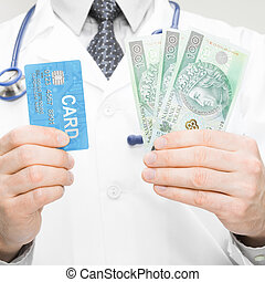 Doctor holding money and credit card in his hand - closeup studio shot - 1 to 1 ratio
