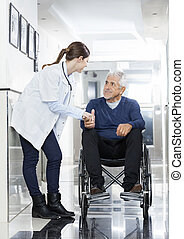 Doctor Holding Senior Man's Hand On Wheelchair