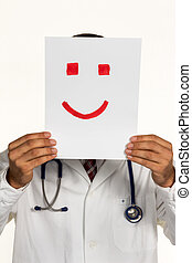 doctor holding smiley face before - a doctor holds a smily...