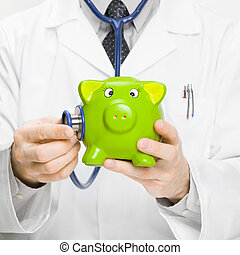 Doctor holding stethoscope and piggybank in hand - medical ...