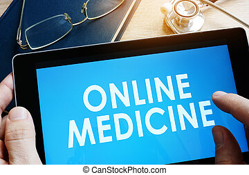 Doctor holding tablet with words online medicine.