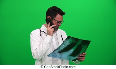 Doctor Holding X Ray Results And Talking On The Phone On A...