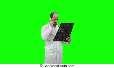 Doctor holding Xray results and talking to the patient on the phone on a Green Screen, Chroma Key.